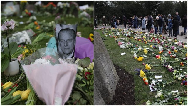 People look at flowers left outside Windsor Castle, Berkshire, following the announcement of the death of the Duke of Edinburgh at the age of 99 (Getty Images)