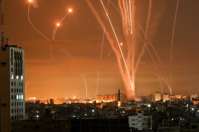 Rockets light up the night sky as they are fired towards Israel from Beit Lahia in the northern Gaza Strip (Photo by MOHAMMED ABED/AFP via Getty Images)
