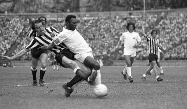 Newcastle United defender Frank Clark tackles Pele during the challenge match in Hong Kong. Pic courtesy of Paul Joannou/NUFC archive.