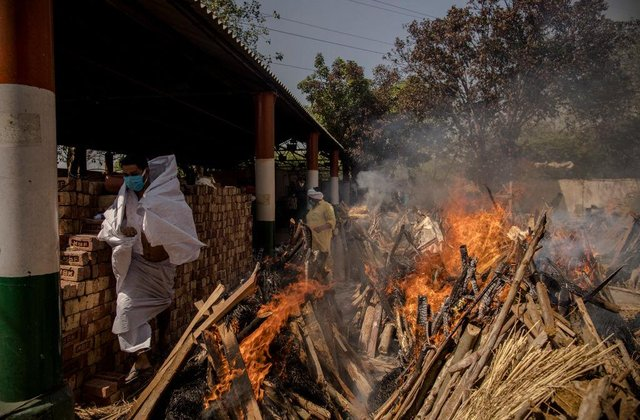 A priest (L) who helps performing last rites, runs to avoid the heat from the multiple burning funeral pyres of patients who died of the Covid-19 coronavirus disease at a crematorium on April 24, 2021 in New Delhi, India.