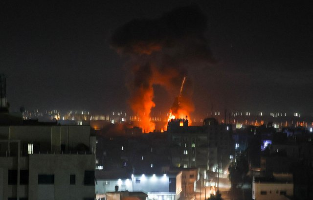 Explosions light-up the night sky above buildings in Gaza City as Israeli forces shell the Palestinian enclave (Photo by MAHMUD HAMS/AFP via Getty Images)