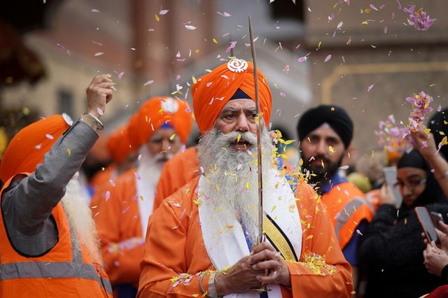 Sikh devotees throw flower petals as sword bearers parade through the streets of Walsall to celebrate Vaisakhi in 2018 (Photo: Christopher Furlong/Getty Images)
