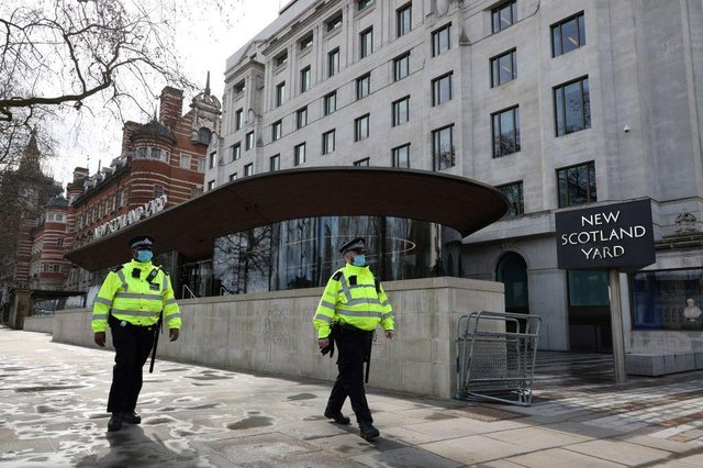 Police officers wearing face coverings due to Covid-19 walk past New Scotland Yard, the headquarters of the Metropolitan Police Service. Officer Benjamin Hannam was found guilty of being a member of banned group National Action.