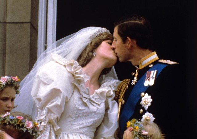 The newly married Prince and Princess of Wales kissing on the balcony of Buckingham Palace after their wedding ceremony (Photo: PA Wire/PA Images)