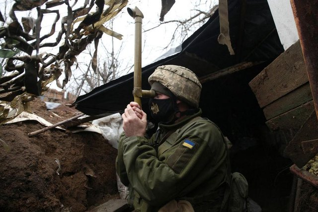 TOPSHOT - A Ukrainian serviceman stands guard at a position on the frontline with Russia backed separatists near small city of Marinka, Donetsk region on April 12, 2021. - Ukrainian soldiers have been killed in clashes with pro-Russia separatists in Ukraine's war-torn east, its military said on April 12, 2021, as Kiev again accused Moscow of massing tens of thousands of soldiers on its border. (Photo by STR/AFP via Getty Images)