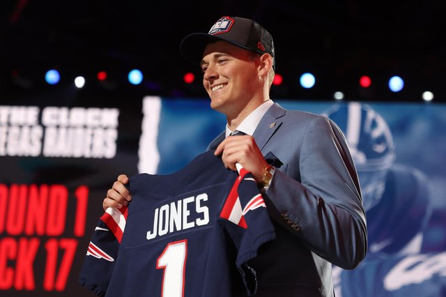 Mac Jones poses onstage after being selected 15th by the New England Patriots during round one of the 2021 NFL Draft at the Great Lakes Science Center on April 29, 2021 in Cleveland, Ohio. (Pic: Getty Images)