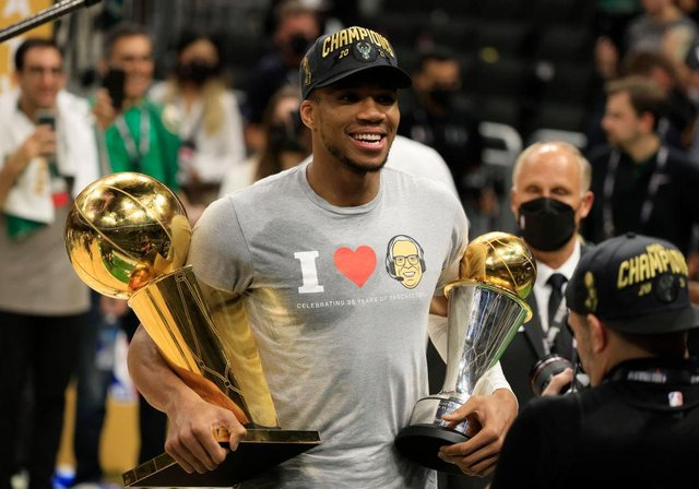 Giannis Antetokounmpo holds the Bill Russell NBA Finals MVP Award and the Larry O'Brien Championship Trophy after defeating the Phoenix Suns in Game Six to win the 2021 NBA Finals (Picture: Getty Images)