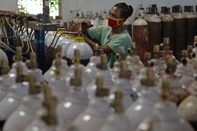 A worker fills medical oxygen cylinders to be transported to hospitals amid Covid-19 coronavirus pandemic at a facility on the outskirts of Chennai.