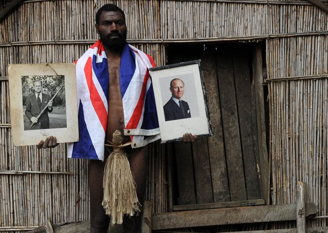 Sikor Natuan, the son of the local chief, holds two official portraits (one holding a pig-killing club, L) of Britain's Prince Philip in front of the chief's hut in the remote village of Yaohnanen on Tanna in Vanuatu on August 6, 2010. (Photo: TORSTEN BLACKWOOD/AFP via Getty Images)