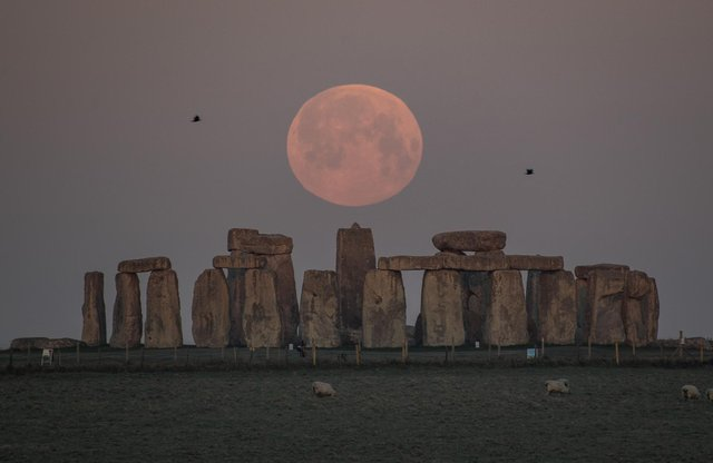 The full moon sets behind Stonehenge in Amesbury, England. (Photo by Finnbarr Webster/Getty Images)