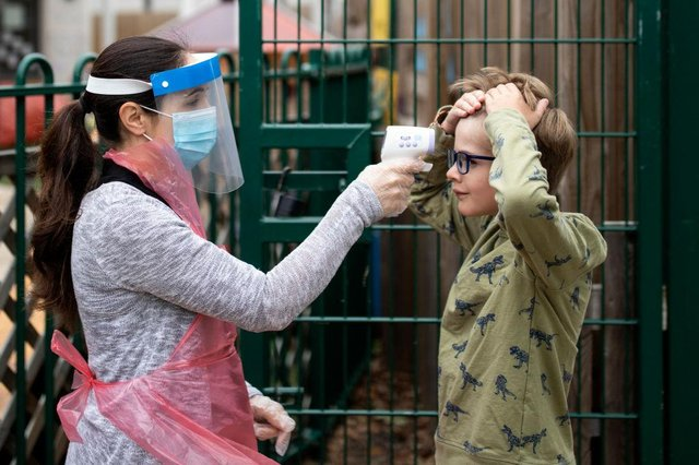 A member of staff takes a child's temperature at a school in June 2020 (Photo: Dan Kitwood/Getty Images)