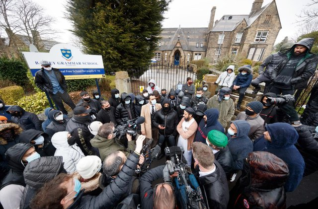 Protesters give a statement to members of the media outside Batley Grammar School in West Yorkshire (PA Media)