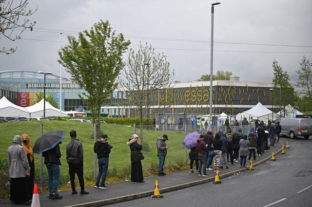 Members of the public queue to receive a Covid-19 vaccine at a temporary vaccination centre at the Essa academy in Bolton (Photo by Oli SCARFF / AFP)