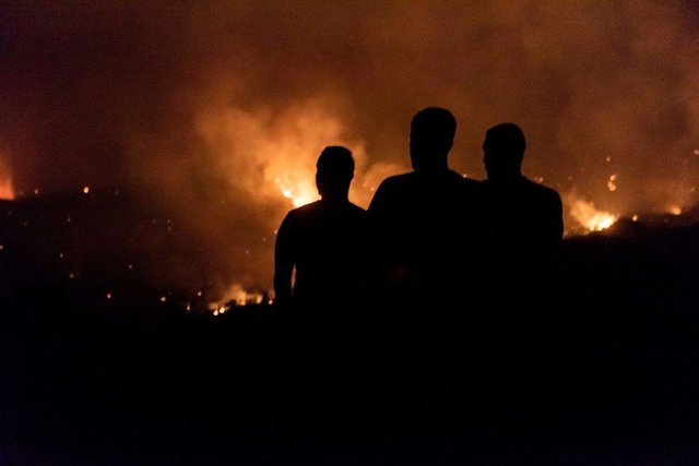 People in the village of Vavatsinia in the Larnaca district of Cyprus watch as the wildfire rages on the nearby hills during the night of 3 July (Picture:  Getty Images)