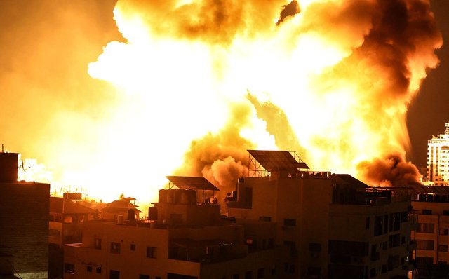 A ball of fire explodes above buildings in Gaza City as Israeli forces shell the Palestinian enclave (Photo by MAHMUD HAMS/AFP via Getty Images)
