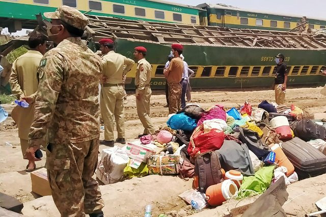 Security personnel stand at the site of a train accident in Daharki area of the northern Sindh province (Photo by AFP via Getty Images)