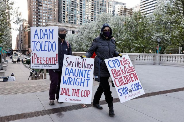 Women walk with signs through the Millennium Park as they protest during a rally on April 15, 2021 in Chicago, Illinois. The rally is held in protest of the killing of 13-year-old Adam Toledo by a Chicago Police officer on March 29th.