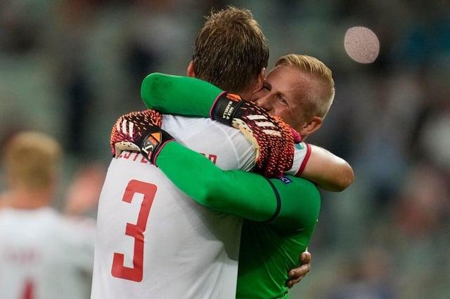 Denmark's goalkeeper Kasper Schmeichel celebrates with defender Jannik Vestergaard. (Photo by DARKO VOJINOVIC/POOL/AFP via Getty Images)