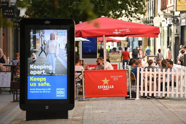 People sit with drinks at outdoor seating at a pub in the centre of Manchester last summer (Getty Images)
