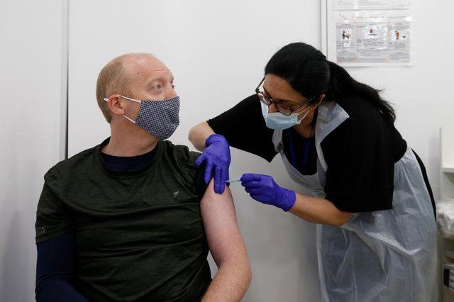 Martin Gillibrand, 45, receives an AstraZeneca vaccination at a Boots pharmacy on Fleet Street in the City of London.