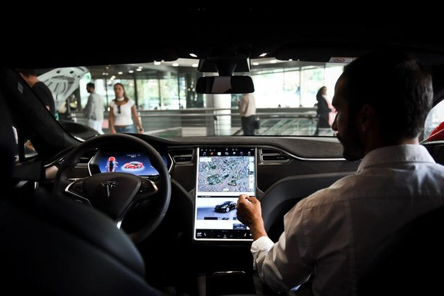 A seller shows the dashboard of the Tesla Model S car at the electric carmaker Tesla showroom of El Corte Ingles store in Lisbon.