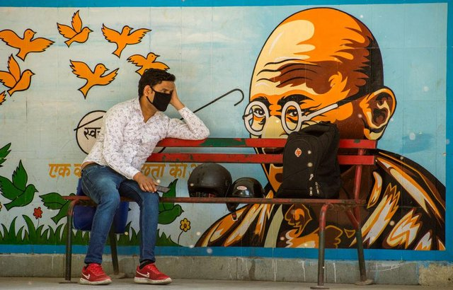 A man wearing a protective mask sits on a New Delhi bench, as India undergoes its first national lockdown in April 2020 (Photo: Yawar Nazir/Getty Images)