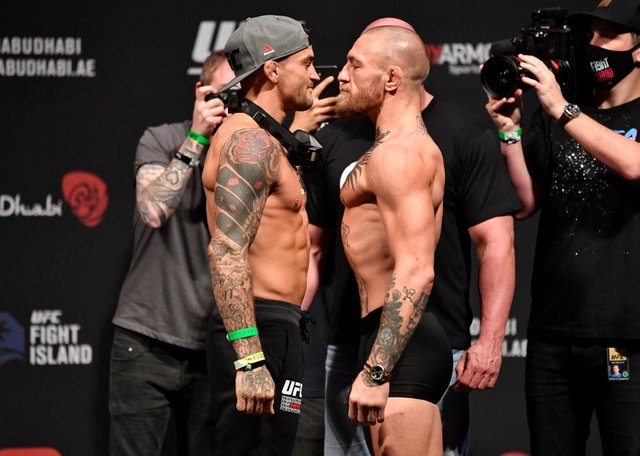 Dustin Poirier and Conor McGregor face off during the UFC 257 weigh-in.