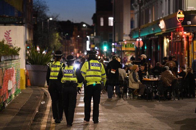 Police officers patrol the streets where customers are enjoying drinks at tables outside the pubs in the Northern Quarter of central Manchester (Photo by OLI SCARFF/AFP via Getty Images)