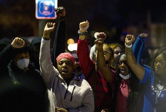 Demonstrators chant around a chalk circle that says Justice for Daunte Wright on April 11, 2021 in Brooklyn Center, Minnesota. Protesters took to the streets after 20 year old Daunte Wright was shot and killed during a traffic stop by members of the Brooklyn Center police.