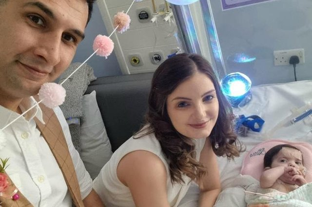 Karim Rezaie, 38, psychological therapist and Louise Rezaie, 30, psychological well-being practitioner pictured on their wedding day with their baby daughter Layla as the bridesmaid (SWNS).