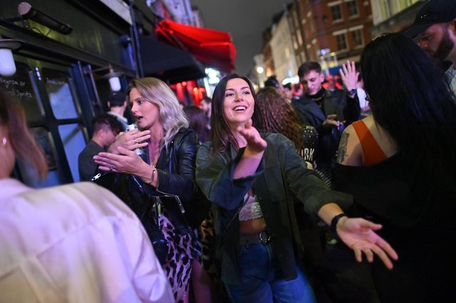 """People should socialise outside as far as possible, maintain social distancing and """"hug cautiously"""" as coronavirus restrictions ease (Photo by JUSTIN TALLIS/AFP via Getty Images)"""
