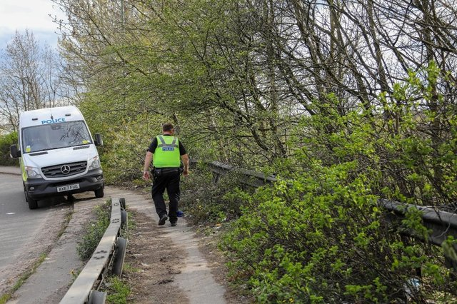 Police at the scene after human remains were discovered in woodland next to the M6 in the Black Country (Photo: SWNS)