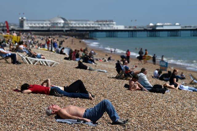 People relax on Brighton in southern England as temperatures rise across the country over the bank holiday weekend (Photo: GLYN KIRK/AFP via Getty Images)