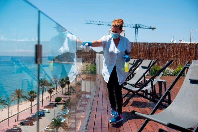 A hotel employee cleans a glass barrier on a terrace overlooking a beach (Photo: JOSEP LAGO/AFP via Getty Images)