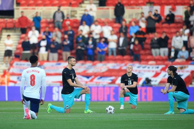 England's midfielder Jude Bellingham (L), Austria's defender Stefan Posch (2L), Austria's midfielder Xaver Schlager (2R) and Austria's striker Marcel Sabitzer take the knee in support of the No Room For Racism campaign ahead of the international friendly football match between England and Austria at the Riverside Stadium.
