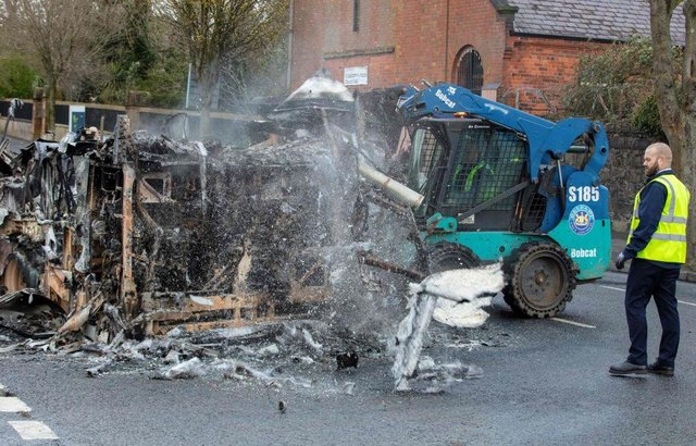 Belfast city council workers clear the remains of a burnt out bus on the loyalist Shankill Road in Belfast on April 8, 2021, after it was set on fire during a night of violence.