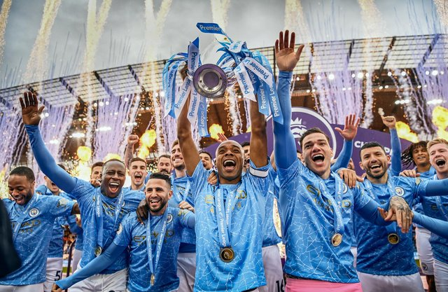Fernandinho of Manchester City lifts the Premier League Trophy with team mates (Photo by Michael Regan/Getty Images)