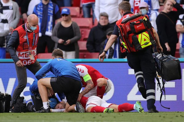 Denmark's midfielder Christian Eriksen receives medical attention after collapsing on the pitch during the UEFA EURO 2020 Group B football match between Denmark and Finland.