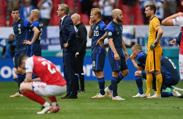 Markku Kanerva, Head Coach of Finland and Teemu Pukki of Finland wait on the pitch as Christian Eriksen (Not pictured) of Denmark receives medical treatment during the UEFA Euro 2020 Championship Group B match between Denmark and Finland on June 12, 2021 in Copenhagen, Denmark. (Photo by Stuart Franklin/Getty Images)