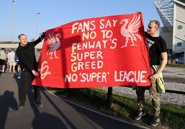 Fans hold up a protest banner against Liverpool FC and the European Super League outside the stadium prior to the Premier League match between Leeds United and Liverpool.