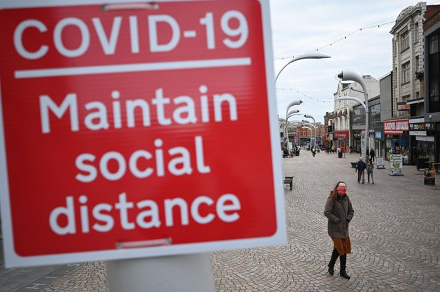 A woman wearing a face mask walks by a sign encouraging social distancing in a street in Blackpool, Lancashire (Photo by OLI SCARFF/AFP via Getty Images)