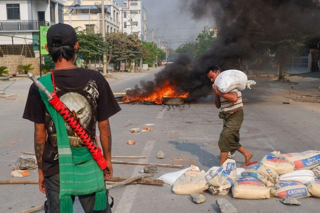 A man carries a sandbag to erect a barricade, as another burns in the distance, as security forces staged a crackdown on demonstrations against the military coup, in Mandalay on 22 March (Picture: Getty Images)
