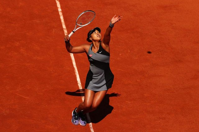 Naomi Osaka serves in her First Round match against Patricia Maria Tig of Romania during Day One of the 2021 French Open at Roland Garros (Photo: Julian Finney/Getty Images)