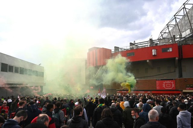 Fans are seen protesting Manchester United's Glazer ownership outside the stadium prior to the Premier League match between Manchester United and Liverpool at Old Trafford. The game was eventually postponed.