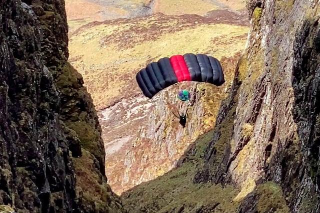 A person base jumps off a ridge atAonach Eagach,Glen Coe, Scotland