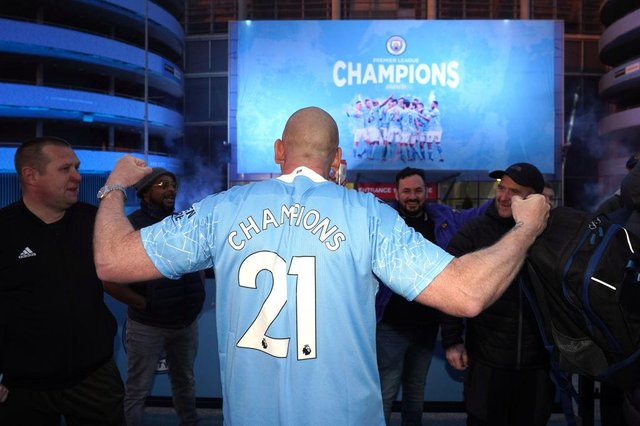 Manchester City fans celebrate outside Etihad Stadium as their team has been confirmed as Premier League champions for the third time in four seasons.