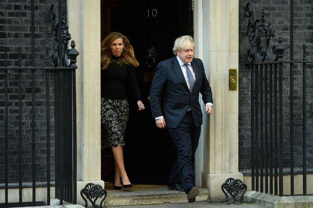Prime Minister Boris Johnson and his partner Carrie Symonds stand outside the door of number 10 Downing Street (Photo by Leon Neal/Getty Images)