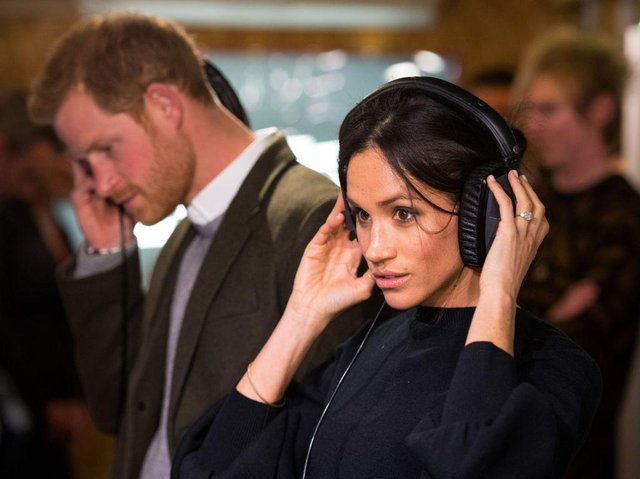 Prince Harry and  Meghan Markle listen to a broadcast through headphones during a visit to Reprezent 107.3FM community radio station in Brixton in 2018 (Photo: DOMINIC LIPINSKI/AFP via Getty Images)