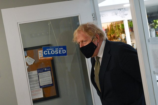 Prime Minister Boris Johnson walks past a sign reading 'we are closed' during a visit to Lemonheads Barber shop, Truro (Photo by Justin Tallis - WPA Pool/Getty Images)