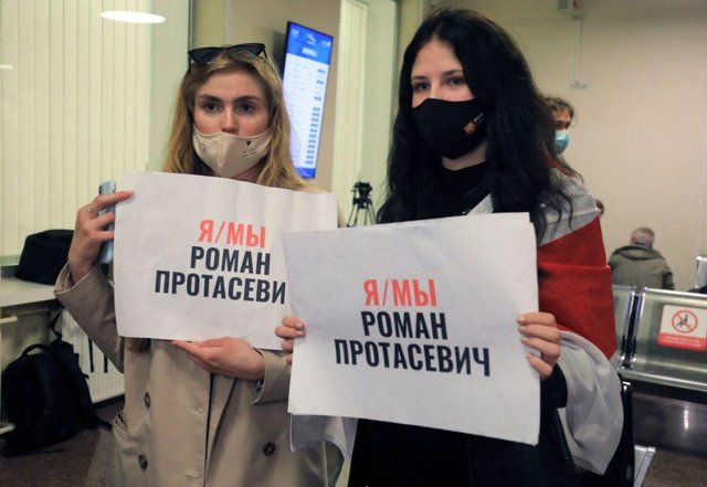 Women with posters reading 'I am/we are Roman Protasevich' in the arrival area as passengers disembark from the Ryanair passenger plane from Athens that was intercepted and diverted to Minsk on the same day by Belarus authorities on 23 May (Photo: PETRAS MALUKAS/AFP via Getty Images)